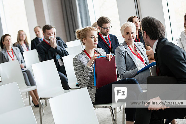 Businessman talking to businesswomen in seminar hall