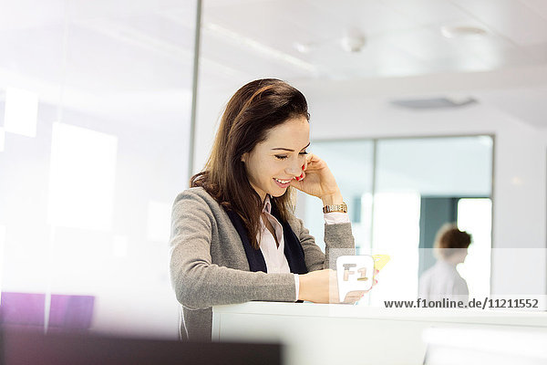 Young businesswoman using mobile phone in office