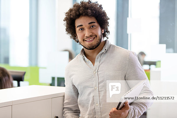 Portrait of smiling young businessman holding laptop in office