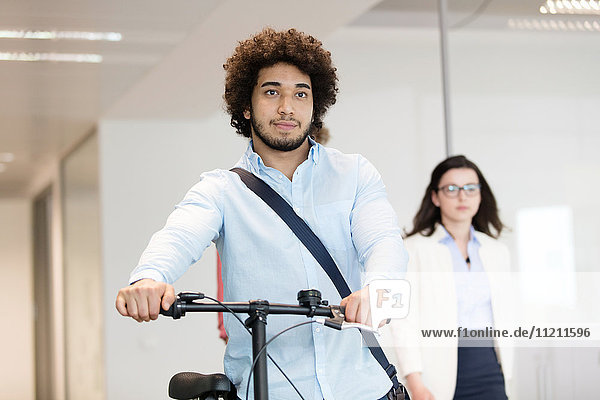Young businessman holding bicycle with female colleague in background at office