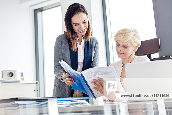Smiling businesswomen reading book at desk in office