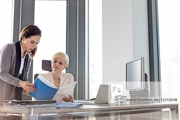Businesswoman and female manager reading book at desk in office