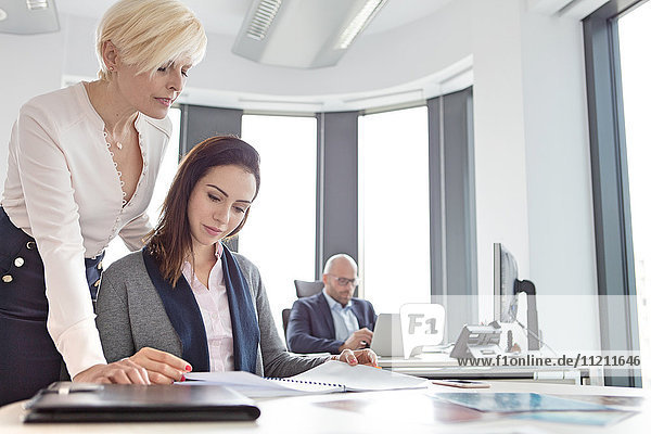 Businesswomen reading project with male colleague in background at office