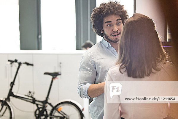 Young businessman talking with female colleague in office