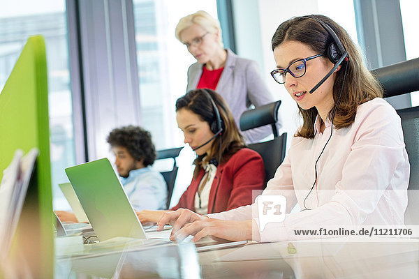 Female customer service representative using laptop while colleagues in background at office