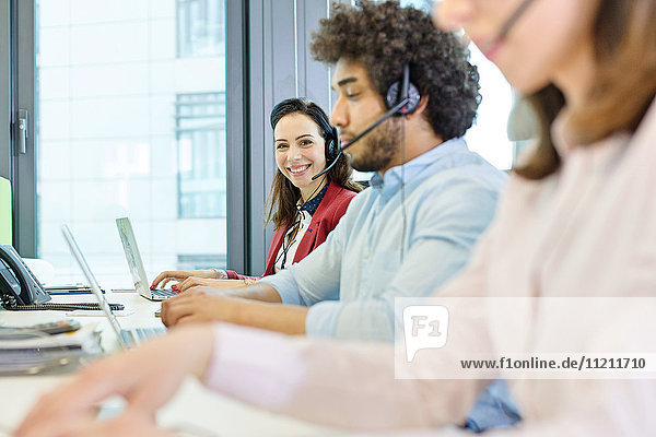 Portrait of smiling young businesswoman using headset and laptop with colleagues in foreground at office