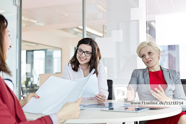 Mature businesswoman discussing with female colleagues at table in office