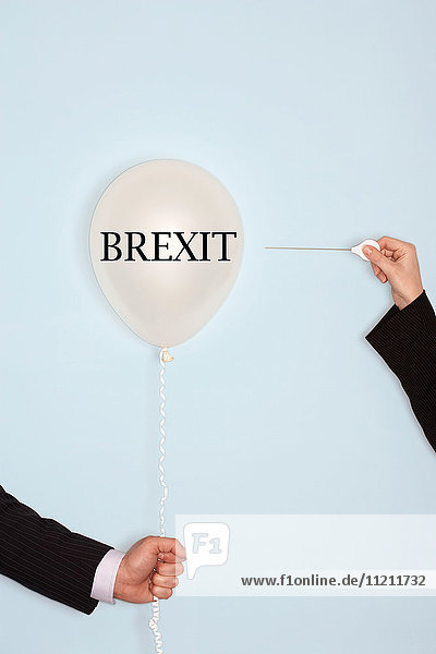 Cropped hands holding needle and popping balloon against light blue background with text saying Brexit