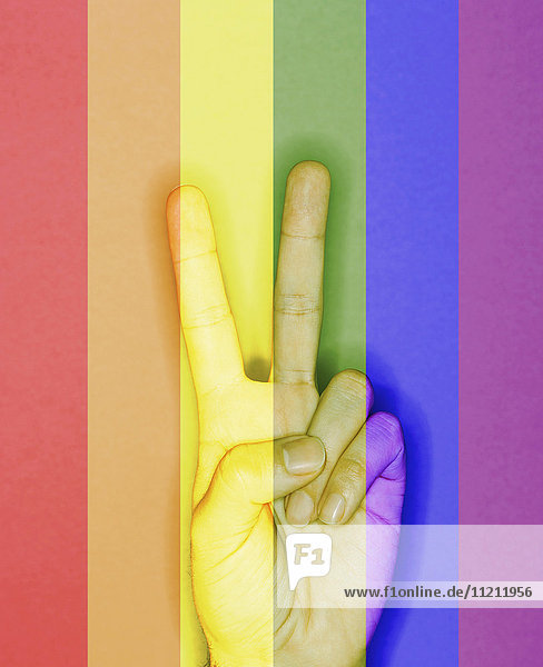 Hand making Peace sign over Rainbow flag