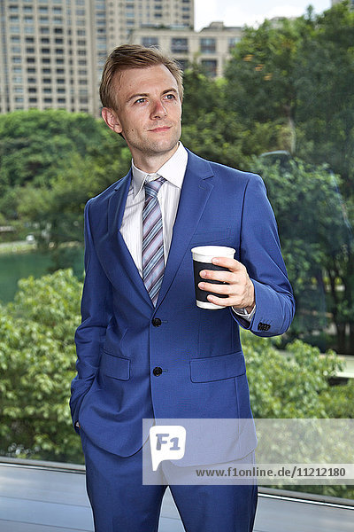 Caucasian businessman with coffee thinking