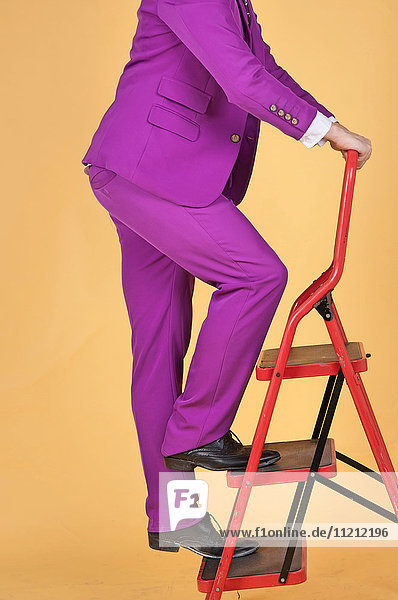 Man in Purple suit climbing ladder