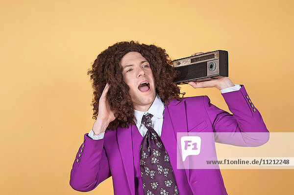 Caucasian man with afro wearing Purple Suit listening to music