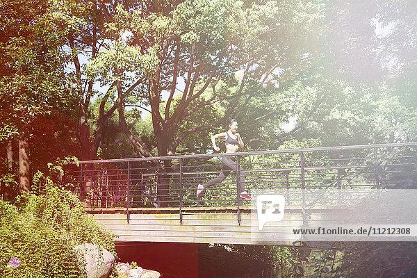 Chinese woman running across bridge