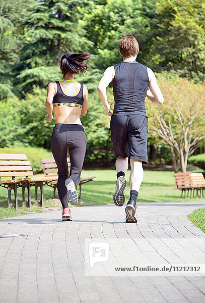 Healthy sports people trail running living an active life. Happy lifestyle couple of athletes training cardio together in summer outdoors. Multi-ethnic group Asian woman with handsome fit man trainer