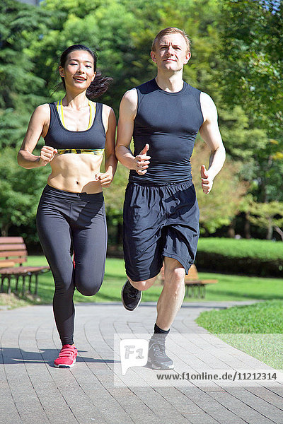 Multi ethnic couple running in park