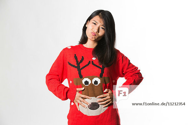 Portrait of woman in Christmas sweater showing she has eaten too much food over gray background