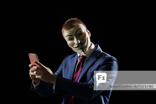 Business man under the mask disguise being Anonymous and implying that he is a hacker or anarchist