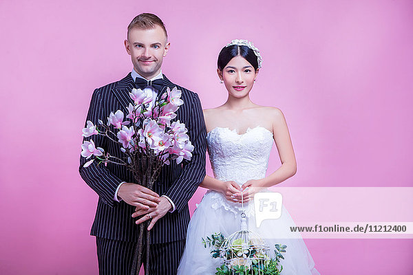 Portrait of multi-ethnic wedding couple holding flowers while standing against pink background