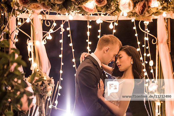 Side view of romantic couple embracing in illuminated gazebo at night