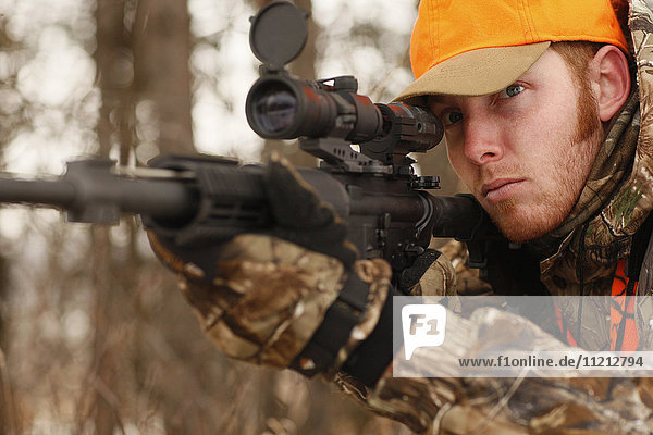 Hunter Aims Rifle While Deer Hunting