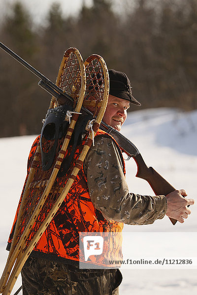 Snowshoe Hare Hunter Carries Snowshoes On His Gun Barrel