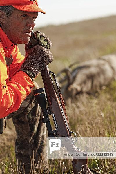 Deer Hunter Resting In Field