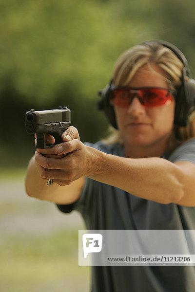 Woman Aims Handgun On Shooting Range