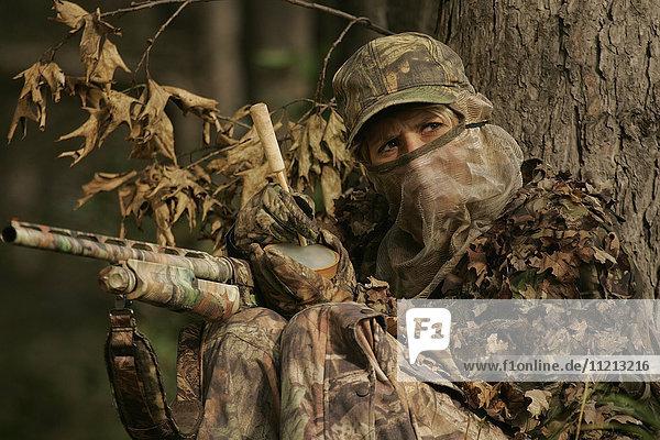 Female Turkey Hunter With Shotgun In A Turkey Blind