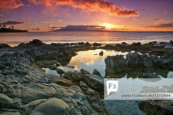 'Sunset reflected in the tranquil tide pools along the coast; Hawaii  United States of America'
