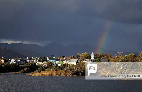 'A rainbow shining through the storm clouds over a town; Sneem  County Kerry  Ireland'