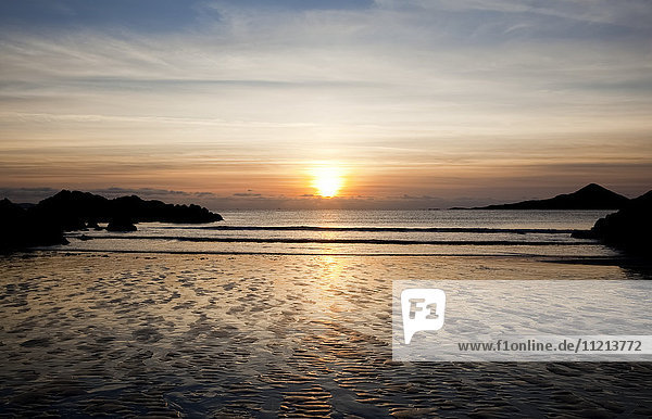 'Sun setting over the horizon with the water washing onto rippled sand on the shore and silhouetted rocks along the coast; Castlecove  County Kerry  Ireland'