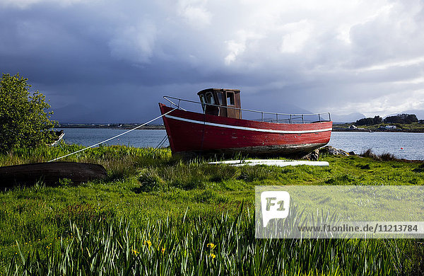 'A red boat tied on the grassy shore along the coast under storm clouds; Roundstone  County Galway  Ireland'
