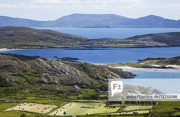 'Farmland in the foreground and mountains across the ocean in the distance; Caherdaniel  County Kerry  Ireland'