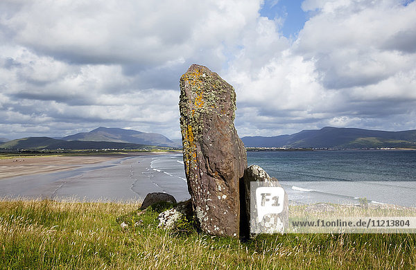 'An ancient standing stone on a ridge overlooking the ocean and coastline  near Waterville; County Kerry  Ireland '