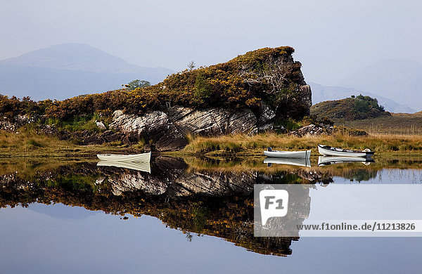 'Canoes moored along the shoreline with a mirror image of a rugged cliff reflected in the water in Killarney National Park; County Kerry  Ireland'