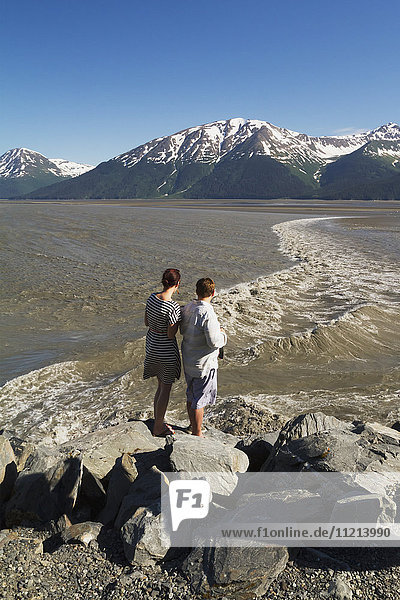 People watching the bore tide in Turnagain Arm. They are at Mile 94 of the Seward Highway at a pull-off. Spring. Southcentral Alaska.