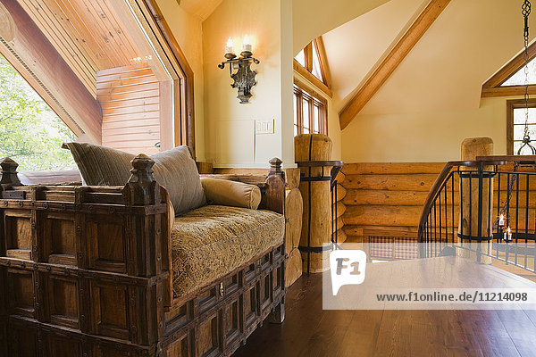 'Medieval style wooden sofa on the upstairs floor mezzanine inside a luxurious cottage style log home; Quebec  Canada'