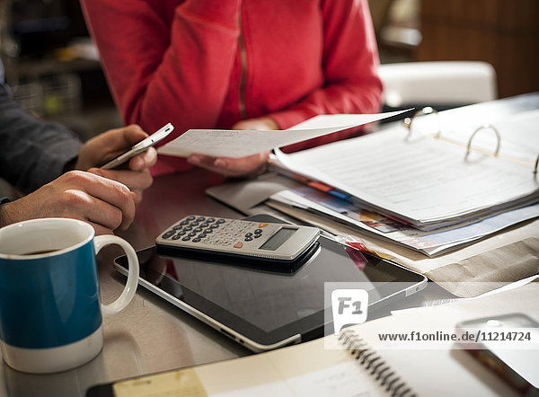 'A man and woman sit at the kitchen table full of documents  calculator and tablet; Regina  Saskatchewan  Canada'
