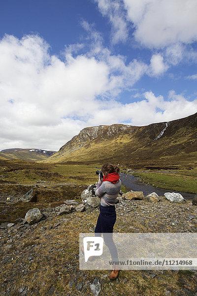 Women photographing Scottish Highland landscape  Scotland