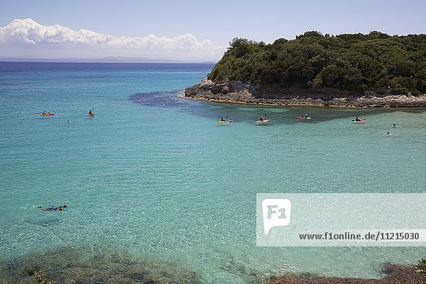 Swimmers bathing in turquoise water of white sand bay bordered by rocky wooded promontory