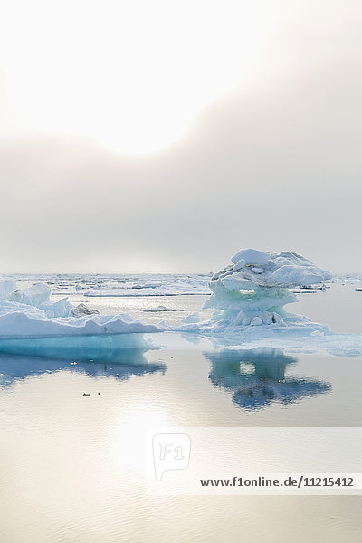 'A foggy sunset over the Arctic Ocean illuminates icebergs on a calm evening; Barrow  North Slope  Alaska  United States of America'
