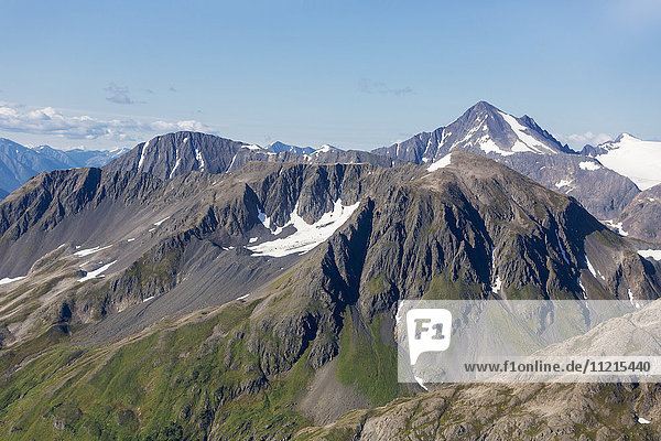 'Peak height view of the Kenai Mountains during summer with little snow on the peaks; Seward  Alaska  United States of America'