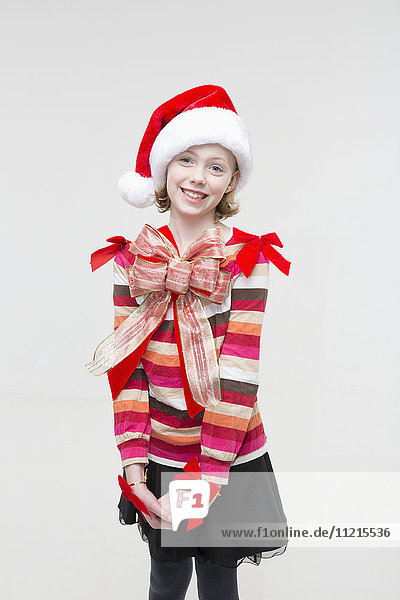 'A young girl wearing a red sweater  santa hat and red bows  posed against a white background; Anchorage  Alaska  United States of America'