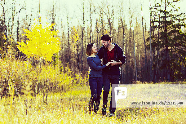 'A young couple walking and pretending to dance in a city park in autumn; Edmonton  Alberta  Canada'