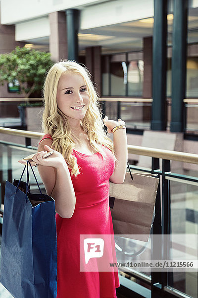 'A beautiful young woman in a dress holding her shopping bags and posing for the camera in an indoor mall; Edmonton  Alberta  Canada'