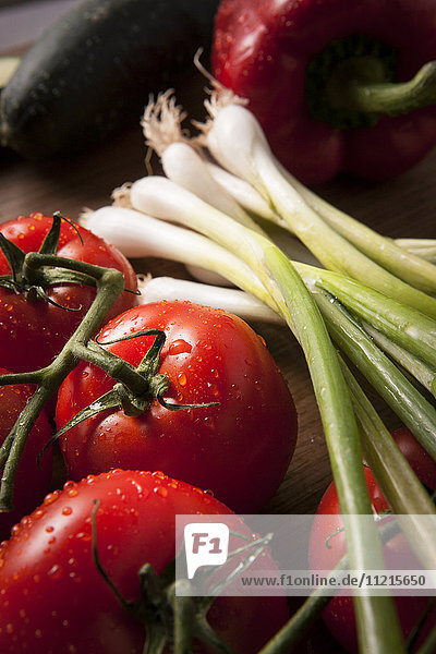 Bright red  ripe tomatoes with water droplets and green onions