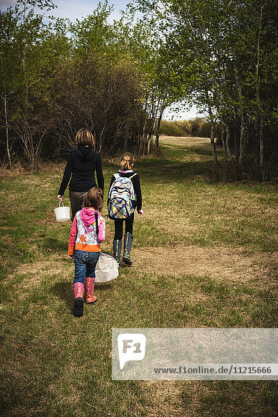'A mother walking with two daughters down a grass trail  holding a pail and net; Saskatchewan  Canada'