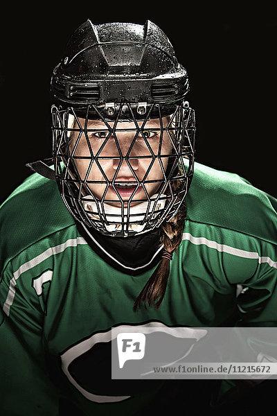 'Ringette player wearing green jersey with helmet and cage; Regina  Saskatchewan  Canada'