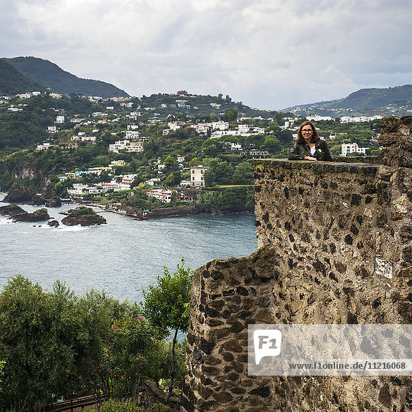 'A woman stands posing from an old stone wall of Aragonese Castle looking out over the coastline of the island of Ischia; Campania  Italy'