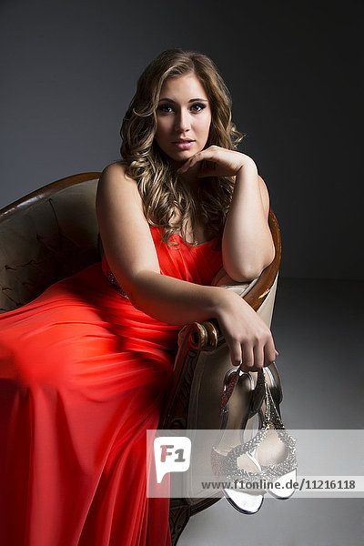 'A beautiful young woman sitting in a chair wearing an orange dress and holding her high heeled shoes while posing for the camera in a darkly lit studio with white background; Edmonton  Alberta  Canada'